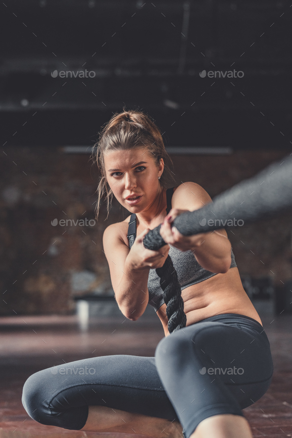 Sporty young girl pulling a rope - Stock Photo - Images