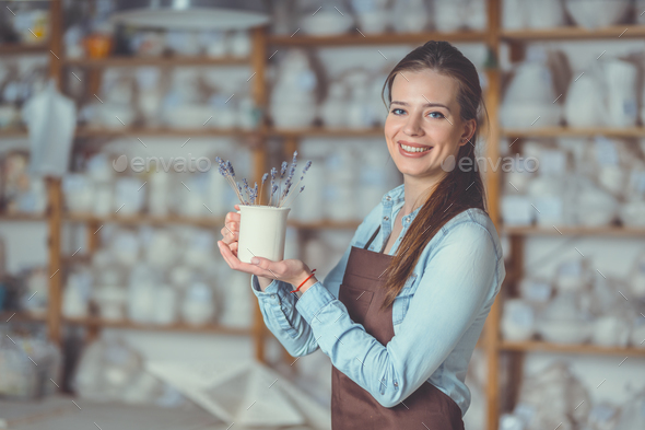 Young girl with a vase in pottery - Stock Photo - Images