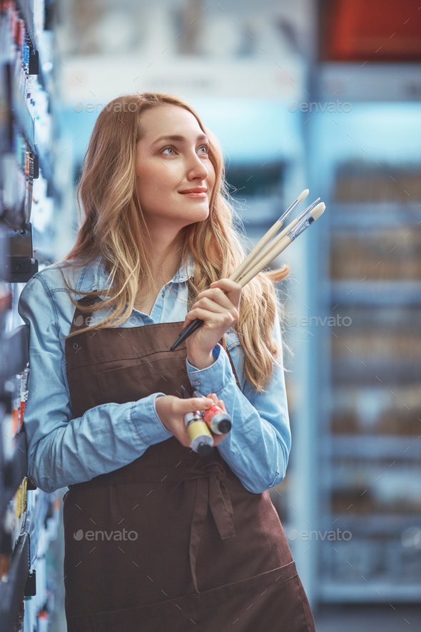 Smiling young girl in an apron indoors - Stock Photo - Images