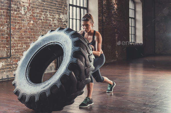Athletic woman with a wheel in the loft - Stock Photo - Images