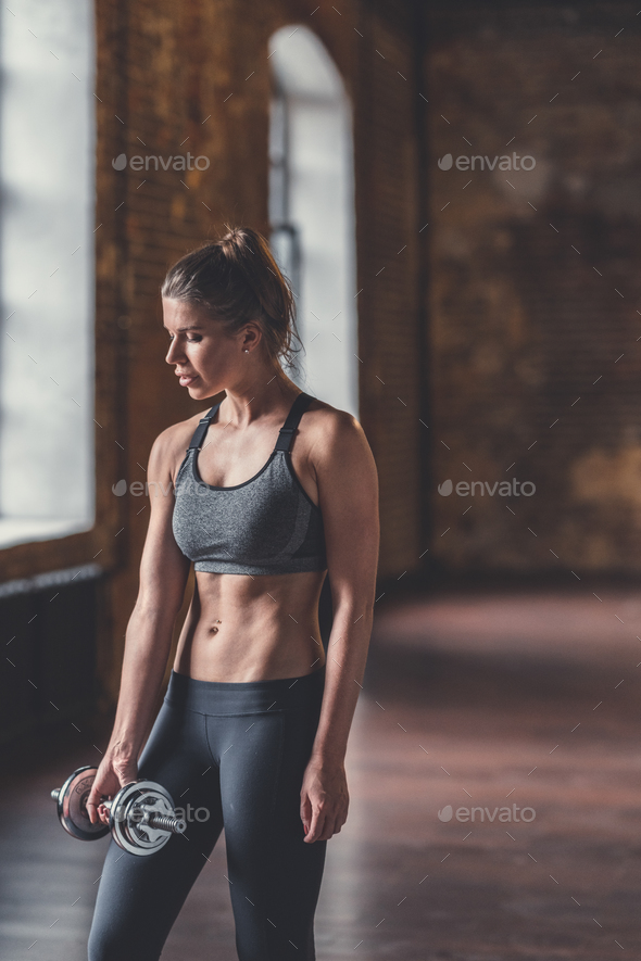 Athletic girl with dumbbells at workout - Stock Photo - Images