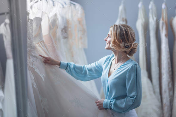 Young girl chooses a wedding dress in the store - Stock Photo - Images