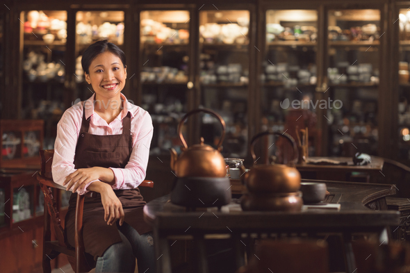 Smiling young woman in an apron - Stock Photo - Images