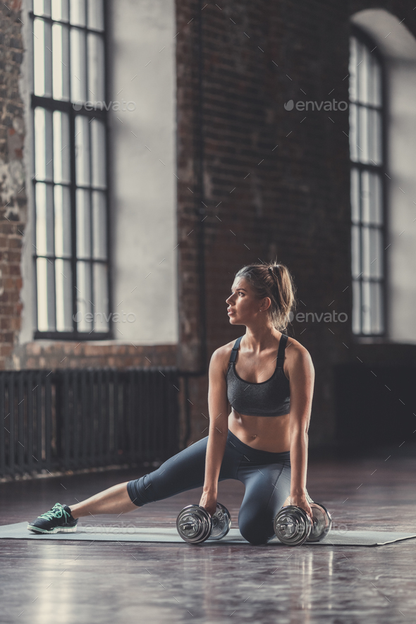 Athletic girl with dumbbells indoors - Stock Photo - Images