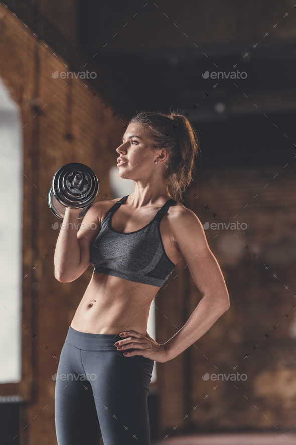Athletic young girl with dumbbells indoors - Stock Photo - Images