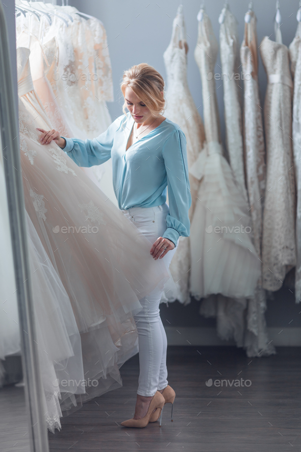 Young woman chooses a wedding dress in the store - Stock Photo - Images