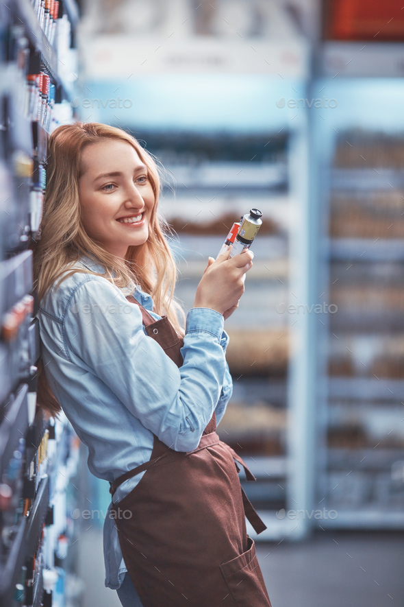 Young girl in an apron in the store - Stock Photo - Images