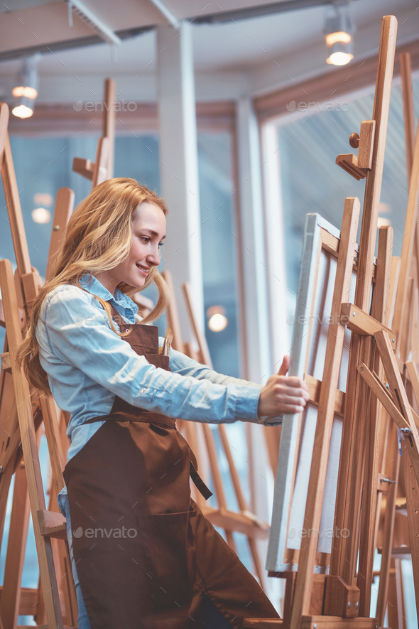 Attractive young woman with easels - Stock Photo - Images