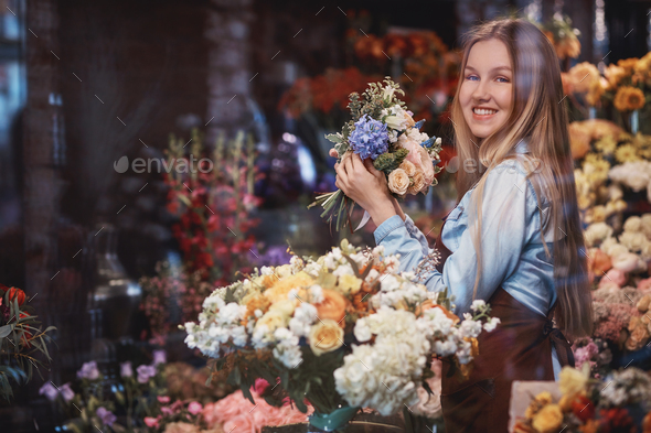 Smiling young florist with flowers - Stock Photo - Images