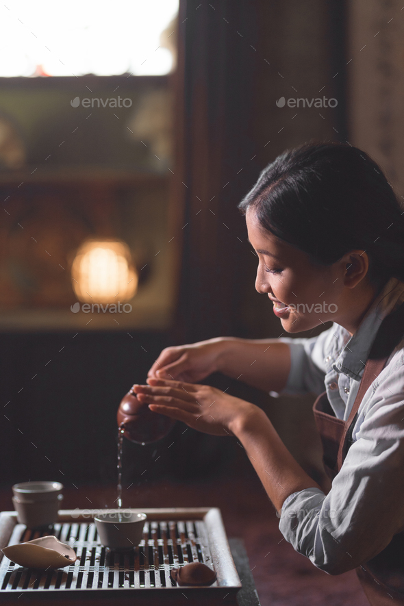 Young tea master pouring tea - Stock Photo - Images