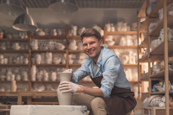 Smiling young man with a potter's wheel - Stock Photo - Images
