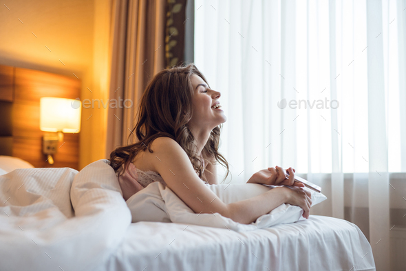 Smiling young girl in bed - Stock Photo - Images