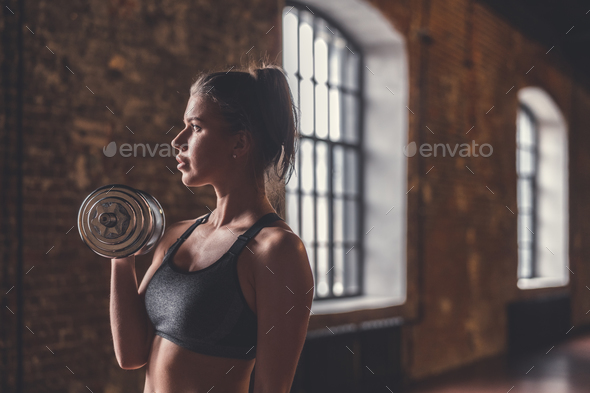 Young girl with dumbbells in the loft - Stock Photo - Images