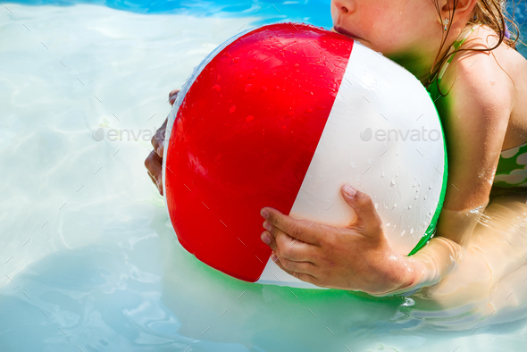 Little girl is playing with a ball in the pool into water on summer vacation in the courtyard - Stock Photo - Images