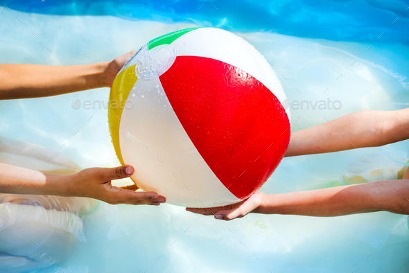 hands of little boy and girl playing with Multi Colored Beach ball in swimming pool - Stock Photo - Images