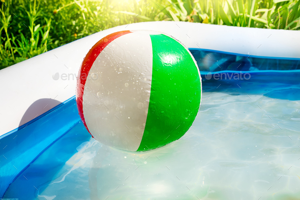 Beach ball floating in swimming pool in the yard. - Stock Photo - Images