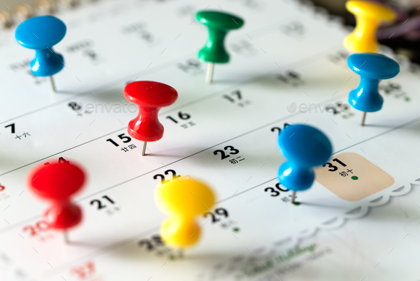 Thumb tack pins on calendar as reminder - Stock Photo - Images