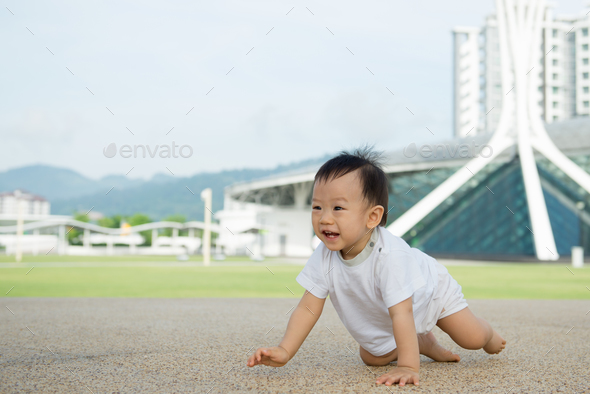 Asian baby boy crawling in park - Stock Photo - Images