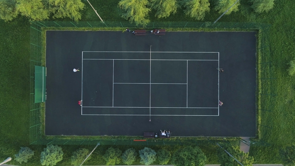Players Play Tennis On A Green Court Aerial Vertical Top Down View