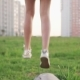 Legs of Little Girl Walking on Concrete Log and Jump on Grass on City Lawn - VideoHive Item for Sale