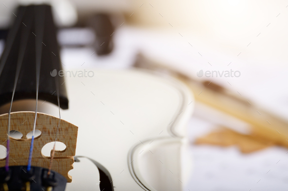 Close view of a white violin dry oak leaves and musical notes on - Stock Photo - Images