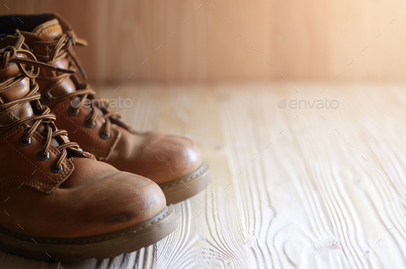Yellow leather used work boots on wooden background closeup. Pla - Stock Photo - Images