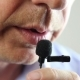 The Man Speaks Into a Small Microphone in a Low Voice - VideoHive Item for Sale