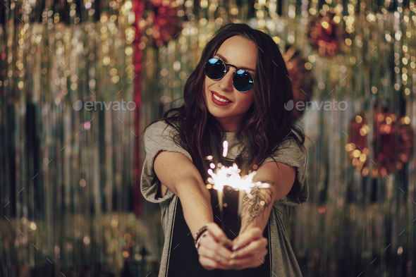 Attractive hipster girl holding sparklers in hands - Stock Photo - Images