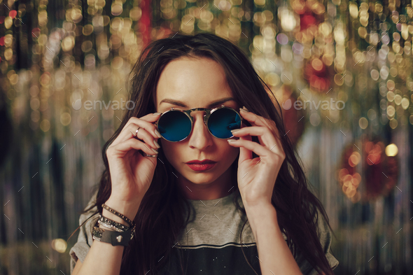Portrait young woman touching fashionable sunglasses - Stock Photo - Images