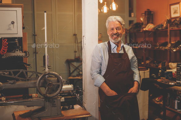 Smiling elderly shoemaker in uniform - Stock Photo - Images