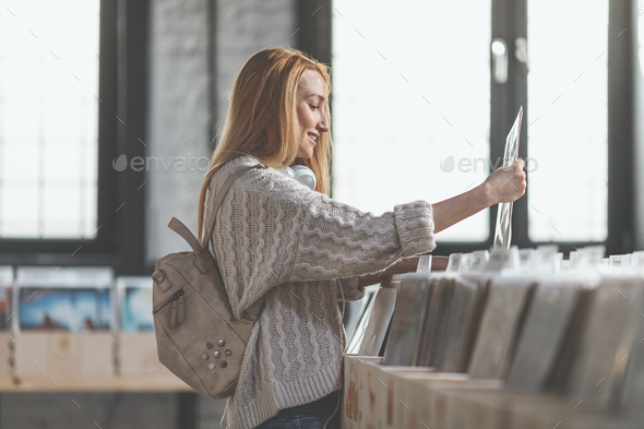 Smiling girl browsing records - Stock Photo - Images