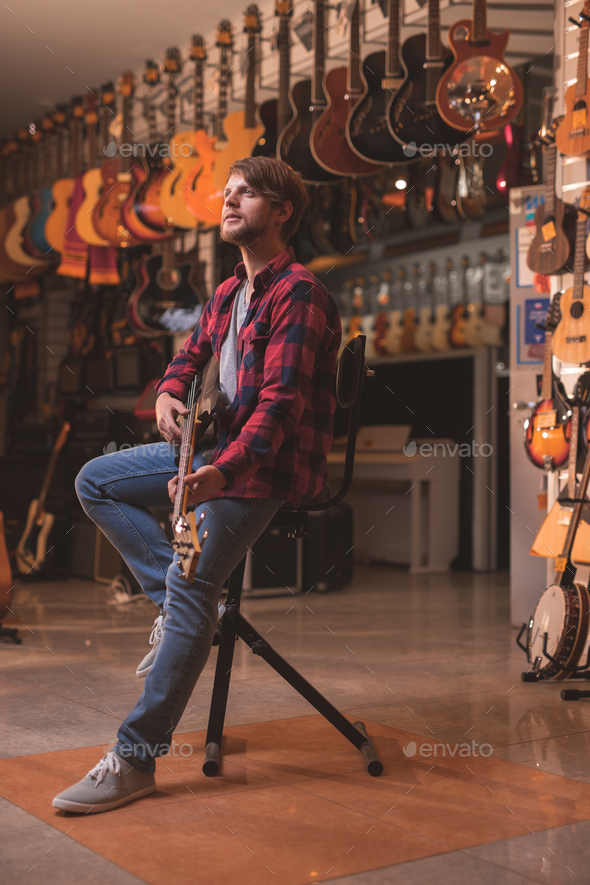 Young man playing the guitar indoors - Stock Photo - Images