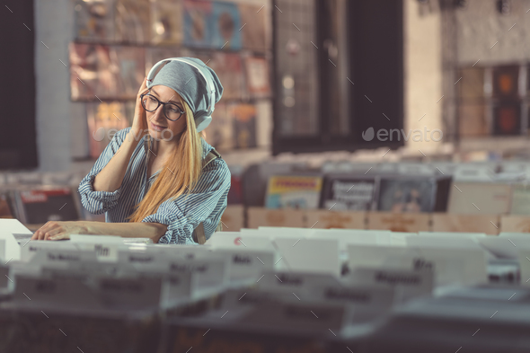 Young girl listening to music in music store - Stock Photo - Images