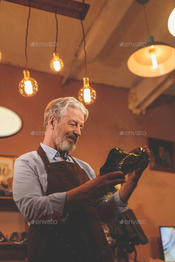 An elderly man with a shoe i - Stock Photo - Images