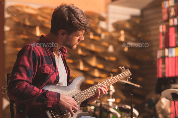 Young man playing bass guitar - Stock Photo - Images