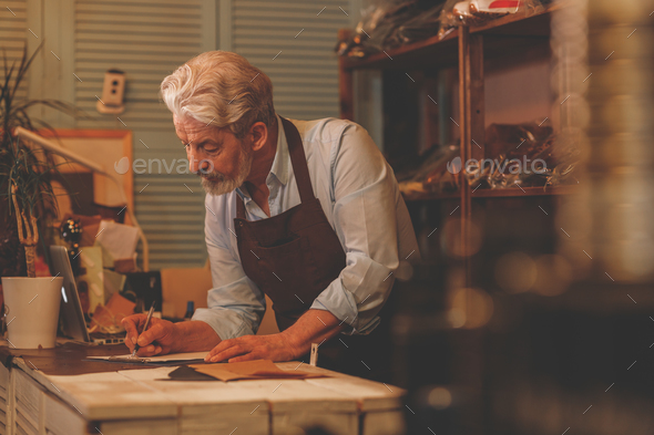 An elderly shoemaker at work - Stock Photo - Images