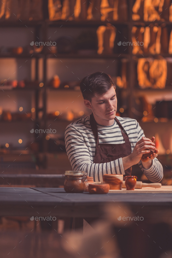Young man in an apron in studio - Stock Photo - Images