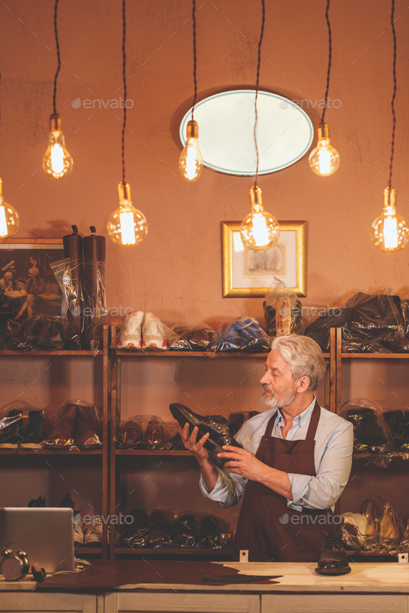 An elderly shoemaker with a shoe - Stock Photo - Images
