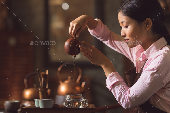 Young woman pouring tea - Stock Photo - Images