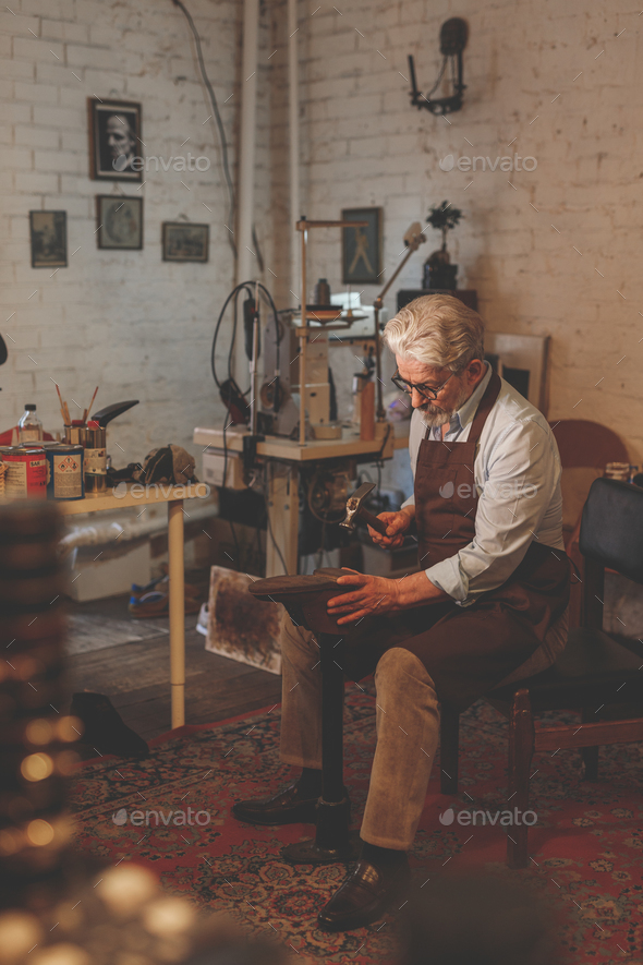 Elder cobbler in the workshop - Stock Photo - Images