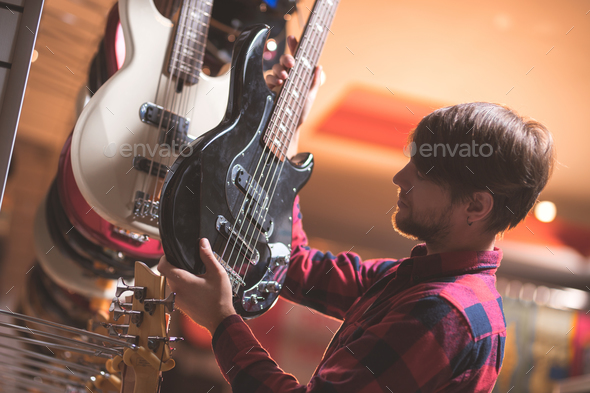 Young man choosing a bass guitar - Stock Photo - Images