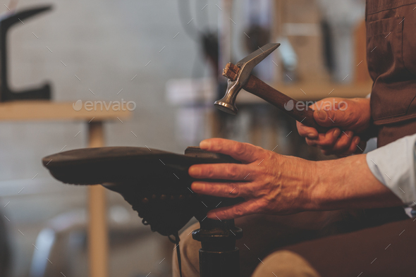 An elderly shoemaker at work close-up - Stock Photo - Images