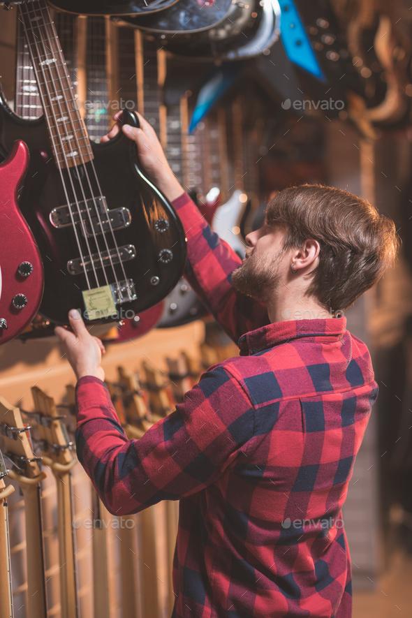 Young musician choosing a bass guitar - Stock Photo - Images