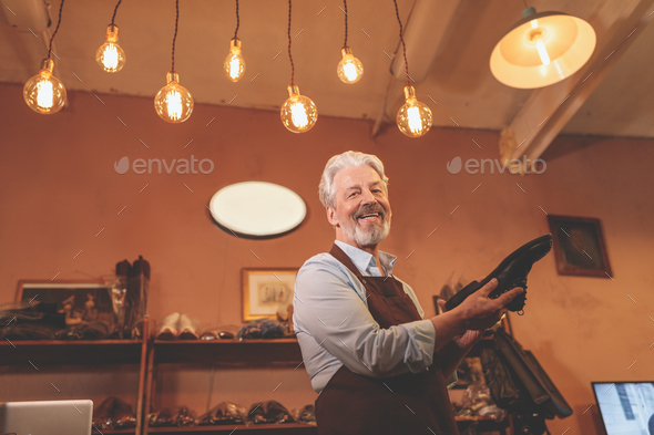 Smiling elderly shoemaker with a shoe - Stock Photo - Images
