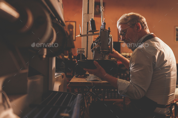 An elderly shoemaker at the factory machine - Stock Photo - Images