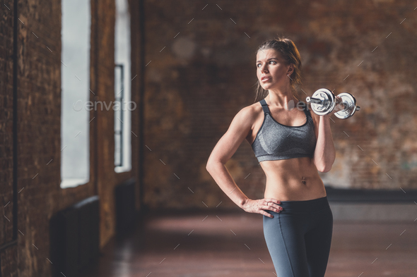 Young sporty woman with a dumbbell in training - Stock Photo - Images