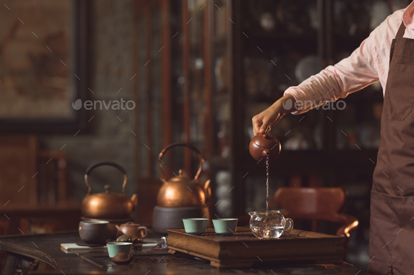 Young professional pouring tea from a teapot - Stock Photo - Images