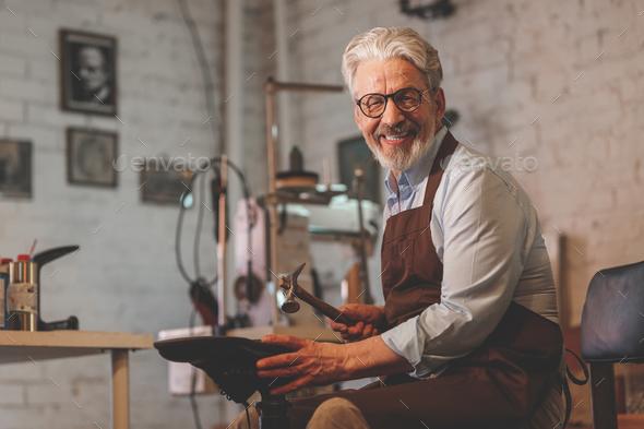 Smiling elderly shoemaker - Stock Photo - Images
