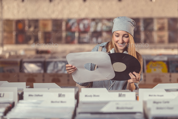 Smiling girl in a vinyl record store - Stock Photo - Images