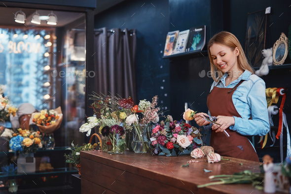 Smiling florist with a bouquet at the counter - Stock Photo - Images